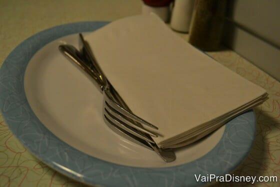 Tá pensando o que? Aqui você que distribui os pratos, talheres e guardanapos na mesa.