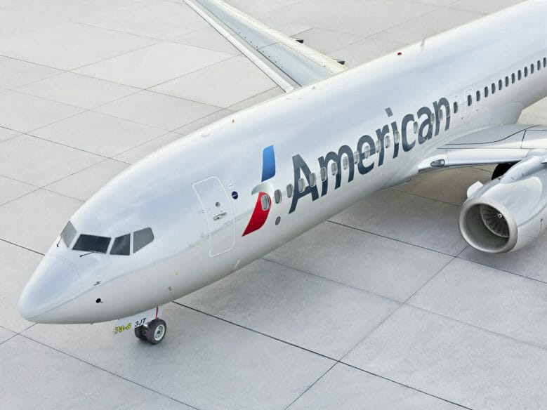 """Imagem de um avião no aeroporto. Ele é branco, tem o logo azul e vermelho da American Airlines e a palavra """"American"""" escrita em preto."""