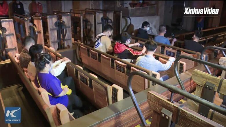 Foto da Disney de Shanghai mostrando os visitantes sentados com uma fileira vaga entre os grupos em uma atração