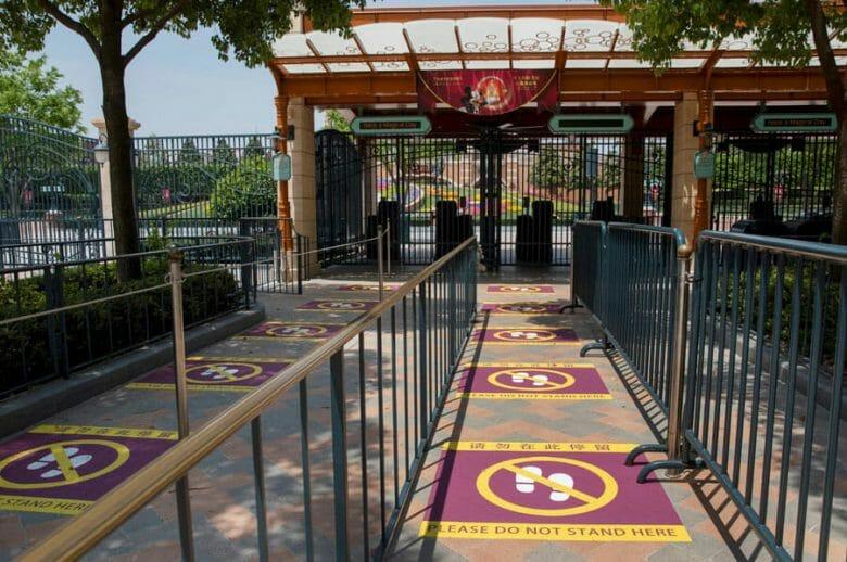Foto da Disney de Shanghai mostrando as marcações no chão colocadas para instruir a respeito da distância que os visitantes devem manter um do outro